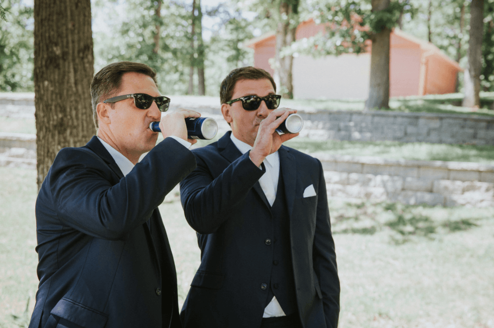 Groom and groomsmen drinking before wedding