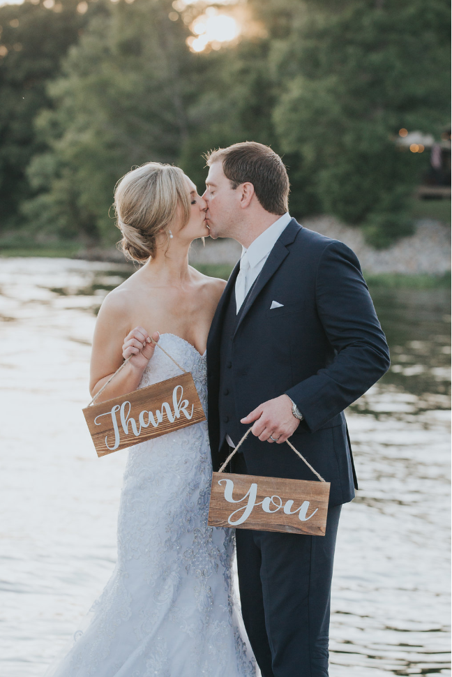 Bride and groom holding a thank you sign next to the lake
