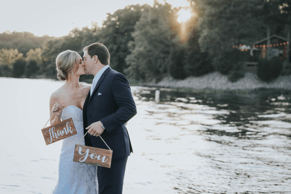 Bride and groom holding a thank you sign next to the lake on their wedding day