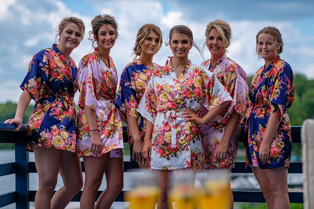 Bridal party drinking cocktails on lakeside bridal suite deck