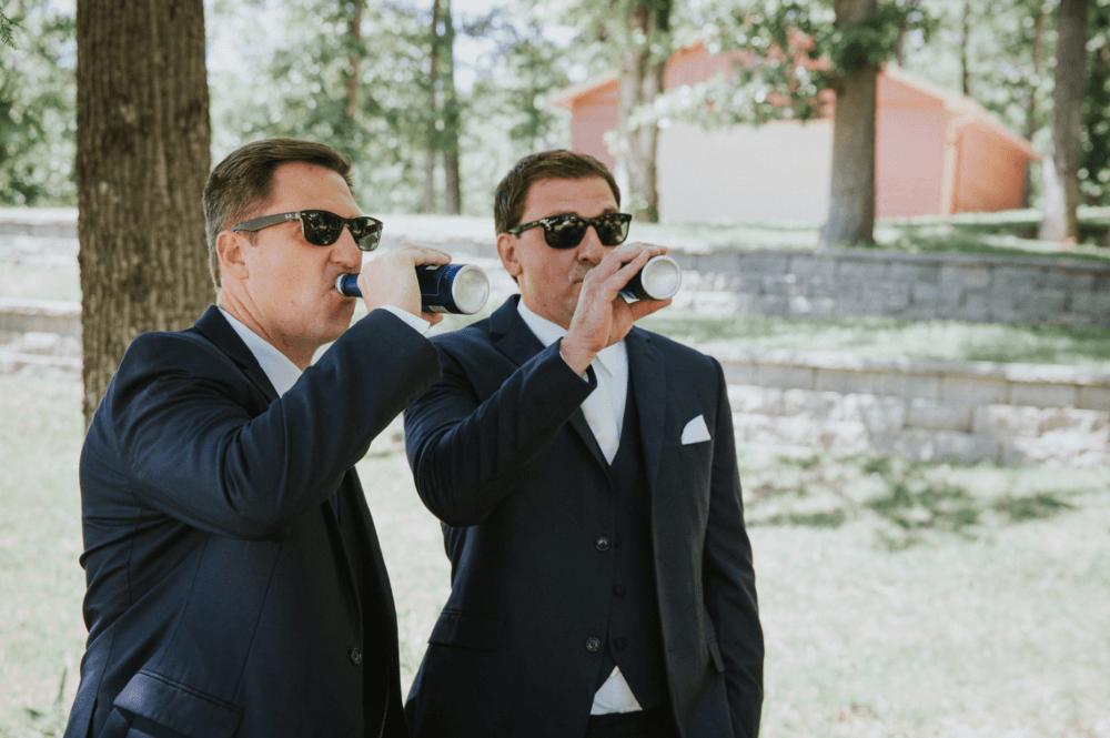 Groom and groomsmen drinking before wedding