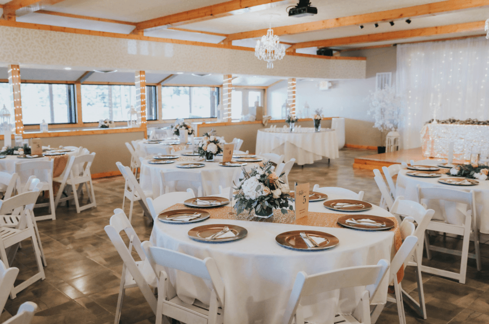 Indoor ballroom with tables set for wedding